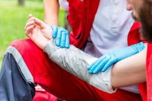 Medical worker treating burns on man's hand. First aid training