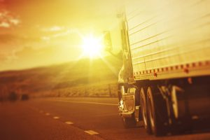 18 wheeler truck driving toward sun