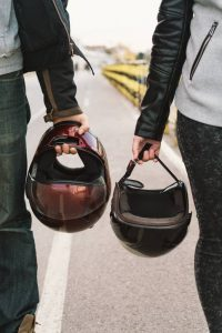 couple holding motorcycle helmets