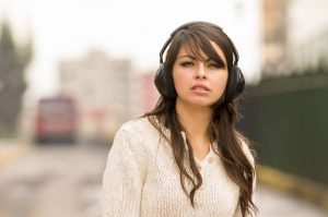 walking in the streets of city wearing headphones
