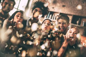 Cheerful young people blowing confetti and smiling while enjoying party together