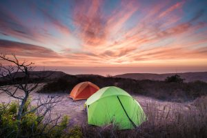 Two camping tents, one green, one orange set up on hill top. Wonderful view of ocean in the Crystal Cove state park.